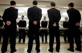Tárgyalóasztalt körülálló egyforma öltönybe öltözött emberek csoportja