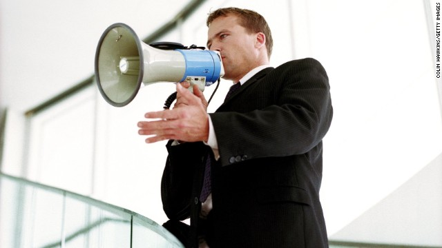 Hangszóróba beszélő öltönyös férfi