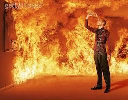 Lángoló tűz mellett álló férfi,aki vízzel locsolja magát egy üvegből