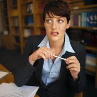 Aggódva és kissé riadtan néző kosztumös hölgy, az íróasztalánál töprengve