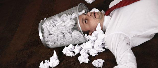 Földön fekvő ideges ember, feje a papírszemetekkel teledobált kukában