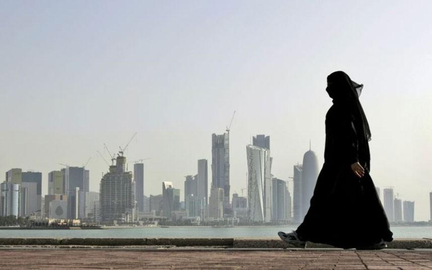 Csadort viselő nő képe, a képen a háttérben arab várossal
