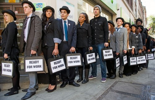 Sorban álló fiatalok, kezükben táblával: