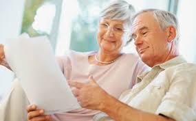 Egy nyugdíjas pár mosolyogva nézi a megtakarítási papírját