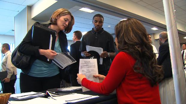 Munkaközvetítőnél egy nő leadja a jelentkezési lapját